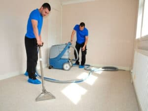 Two men in blue shirts carpet cleaning in a bedroom